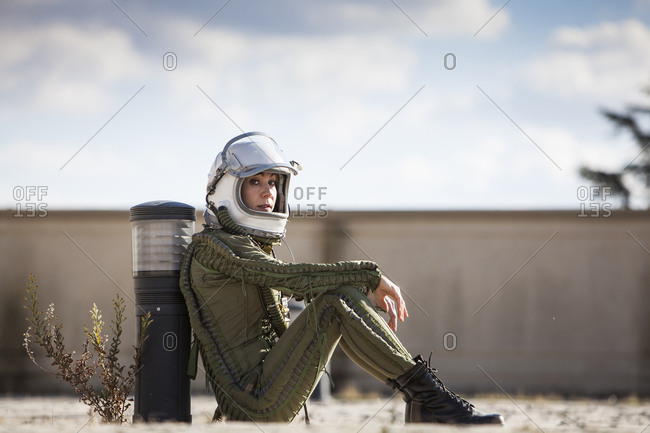beautiful and young blonde dressed as russian aeronautic pilot, sit on the floor and look the camera