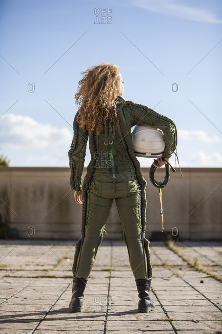 beautiful and young blonde dressed as russian aeronautic pilot, without a helmet, back view