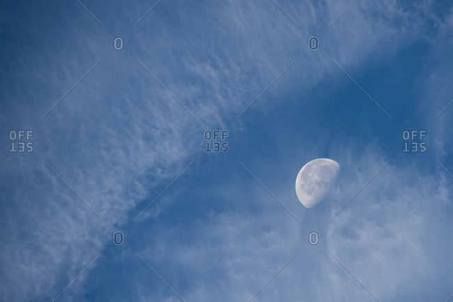 Moon with clouds and blue sky.