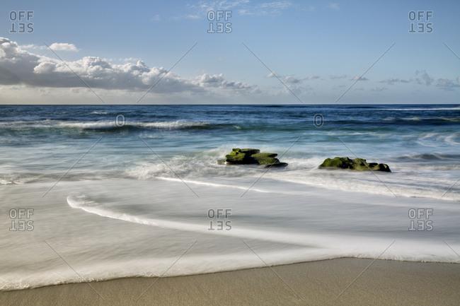USA, California, La Jolla. Rocks and clouds at Whispering Sands Beach