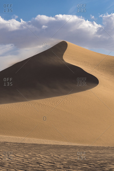USA, California. Windblown sand dune and clouds