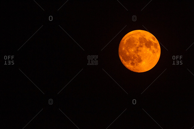 USA, Colorado. Full moon orange from smoke in air.