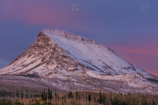 Divide Mountain catching the days first light in Glacier National Park, Montana, USA