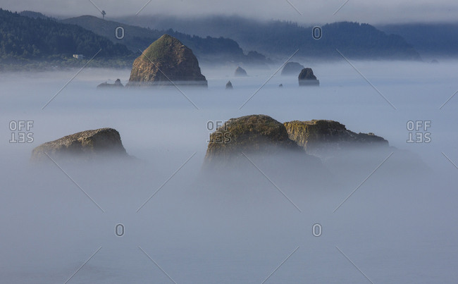 View of Cannon Beach with sea stacks with rising fog from Ecola State Park