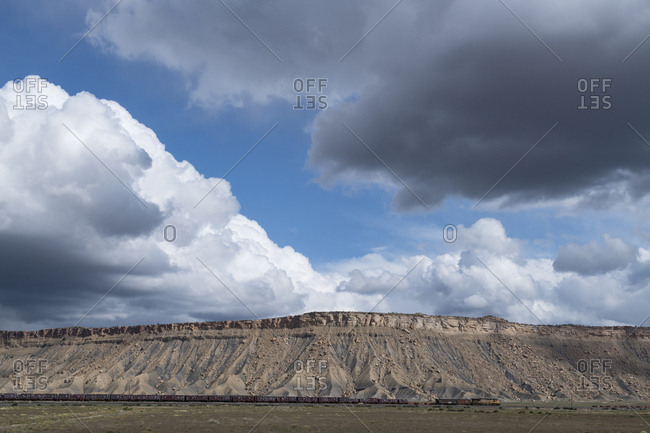 Utah. A freight train passes beneath a rocky butte and cumulus clouds in central Utah.