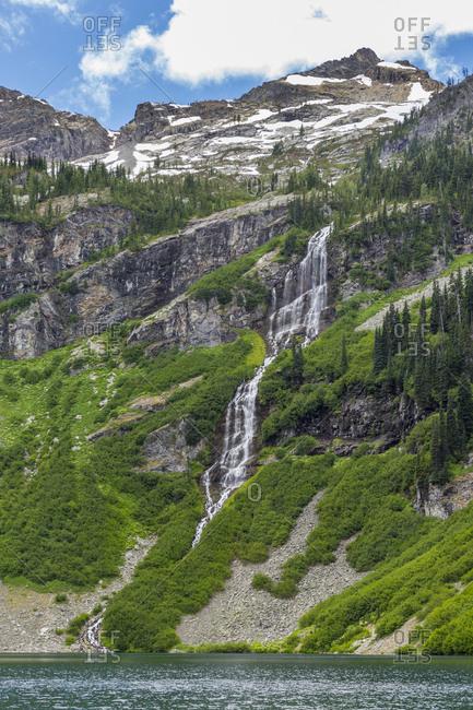 USA, Washington State, North Cascades National Park. Waterfall cascades into Rainy Lake.
