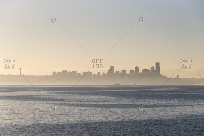 USA, Washington State. Morning fog Seattle. Calm Puget Sound. Variety of boat traffic. Waterfront skyline silhouetted.