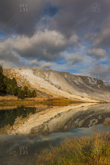 USA, Wyoming. Geothermal mineral deposit formations, grassy meadow, pond and clouds, Mammoth Hot Springs, Yellowstone National Park