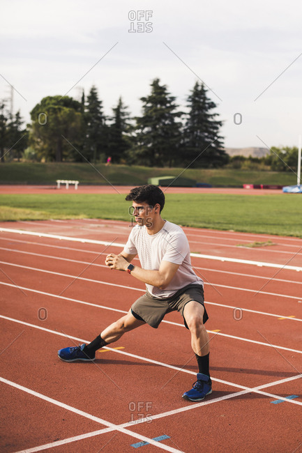 Athlete sitting doing warm-up exercises on a tartan track