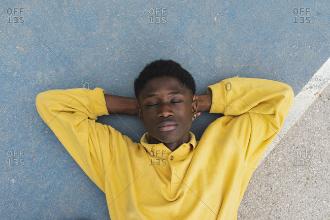Young black man sleeping on floor- with hands behind head