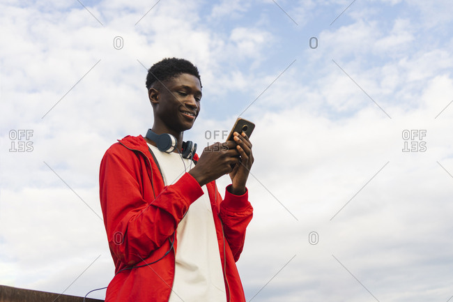 Young man with headphones- reding text messages on his smartphone