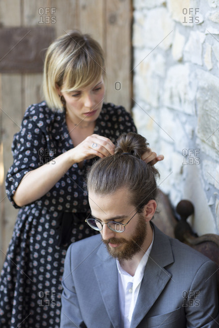 Woman doing hair of young man in grey suit