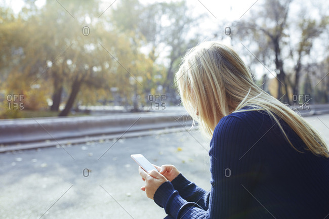 Blond woman using smartphone in autumnal city park