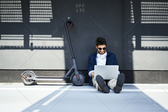 Relaxed young man sitting on the ground besides his electric scooter using laptop