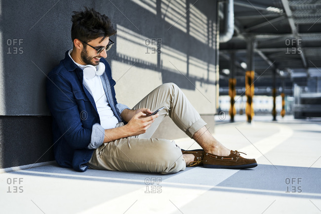Smiling young man sitting on the ground using smartphone
