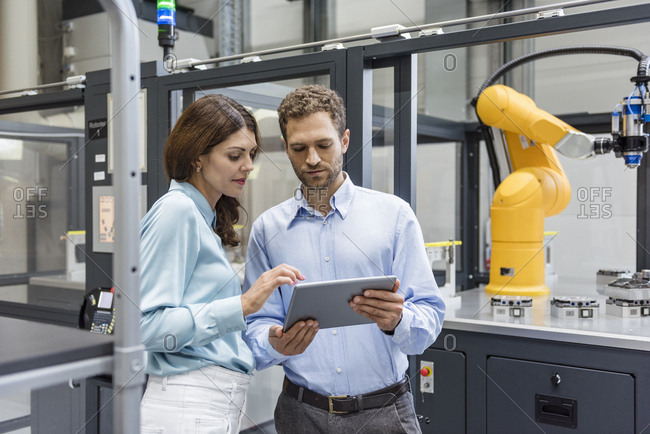 Colleagues in high tech company controlling industrial robots- using digital tablet