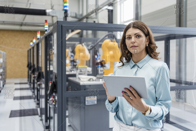 Businesswoman in high tech company controlling industrial robots- using digital tablet