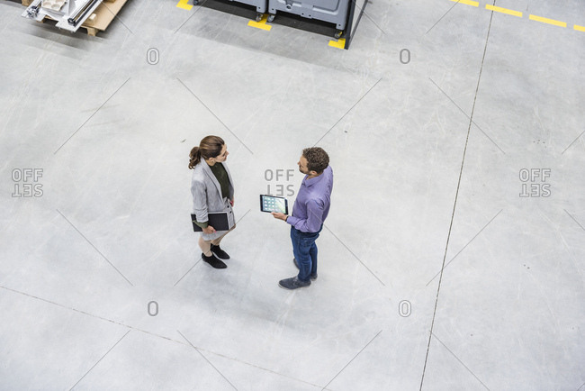 Businessman and woman having a meeting in factory workshop