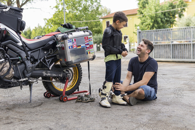 Happy father and son next to a motorbike