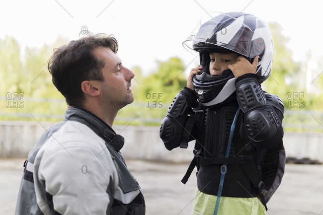 Father watching son putting on motorcycle helmet