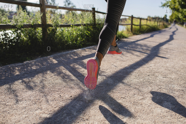 Legs of sportive woman running on path