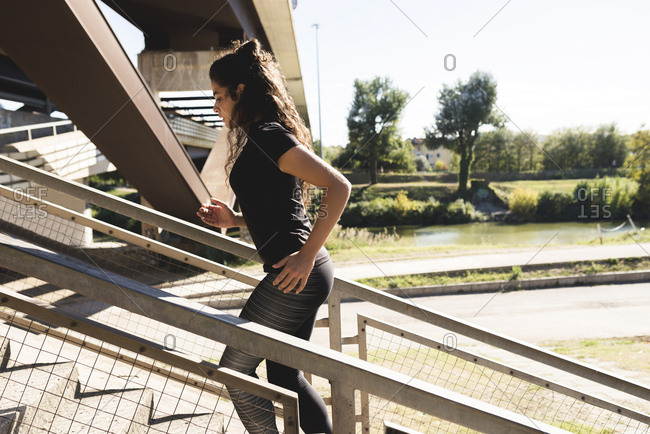 Sportive young woman running on stairs