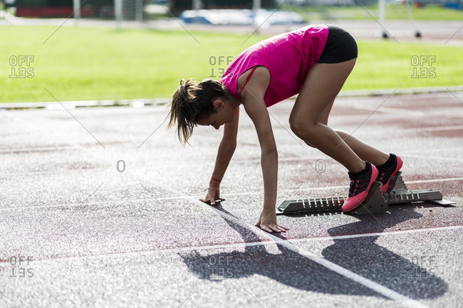 Teenage runner training start on race track