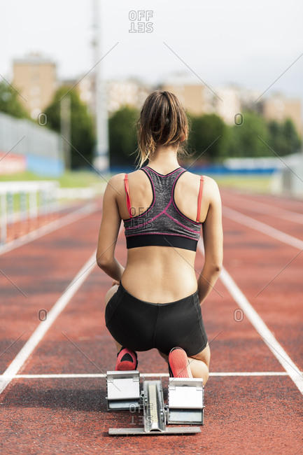 Teenage runner kneeling on starting block