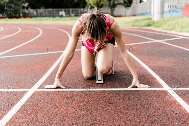Teenage runner in starting position on race track