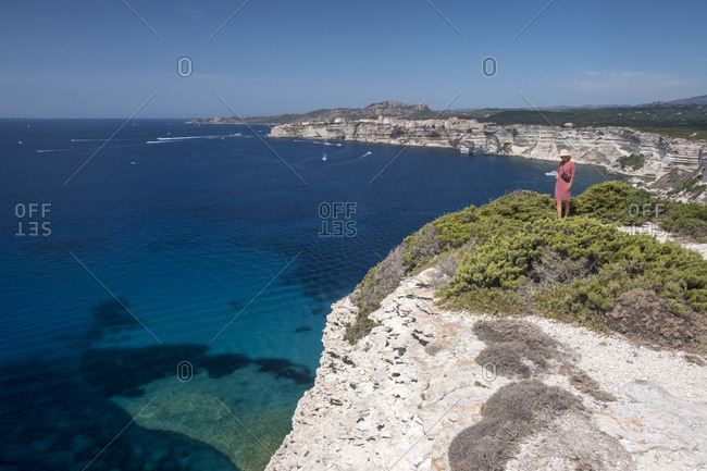 Corsica- Mediterranean coast- woman standing on rocky cliff