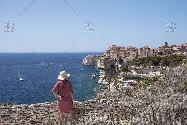 Corsica- Bonifacio- woman standing on viewpoint looking to the city