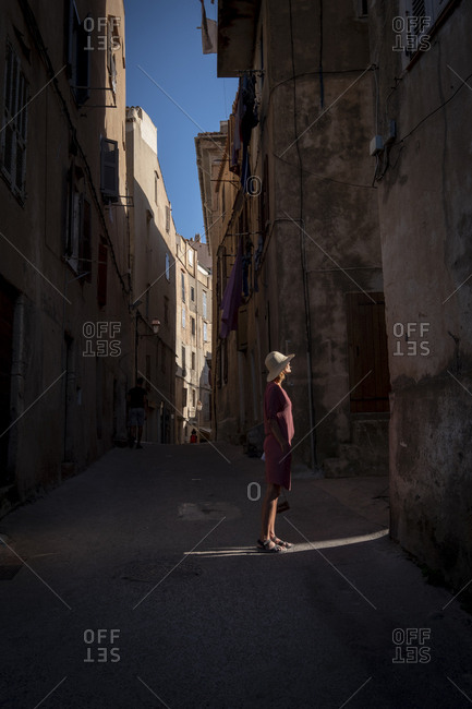 Woman with straw hat sightseeing in Corsica