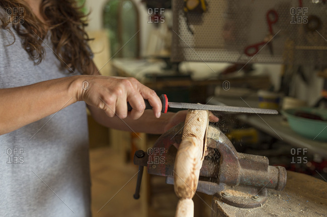 Craftswoman filing a piece of wood in her workshop