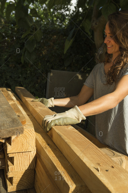Smiling craftswoman wearing protective gloves working with wood