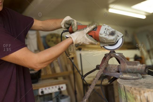 Craftswoman using angle grinder in her workshop