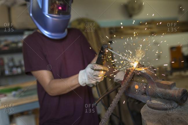 Craftswoman welding metal in her workshop
