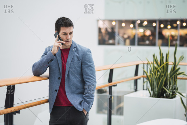 Businessman in lobby of a modern building- using smartphone