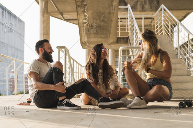 Friends with skateboard sitting down relaxing in the city