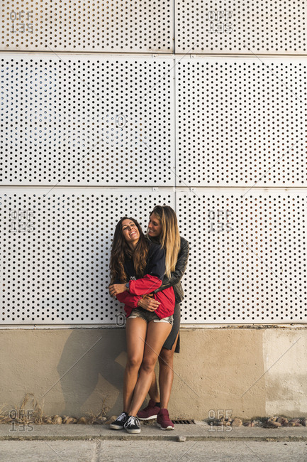 Happy lesbian couple hugging at a wall