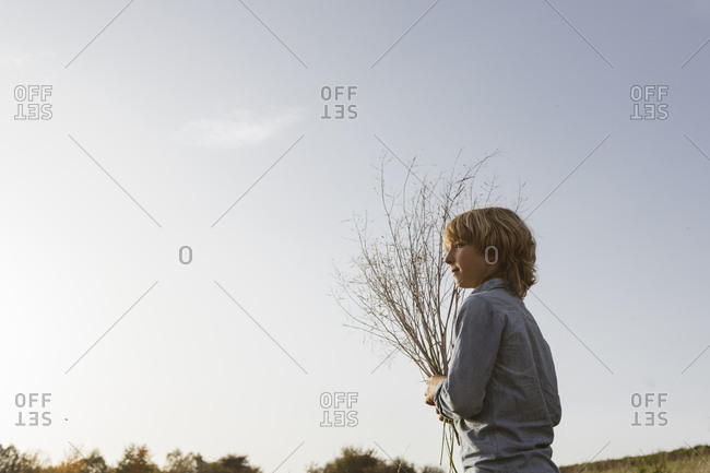 Boy with twigs against sky