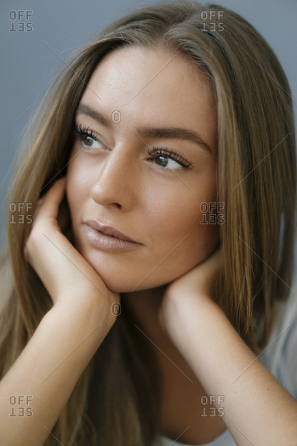 Portrait of daydreaming young woman with head in hands