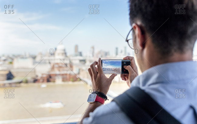 UK- London- man taking a picture of the city from roof terrace