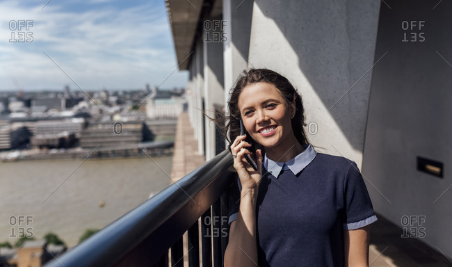 UK- London- smiling woman on the phone on a roof terrace