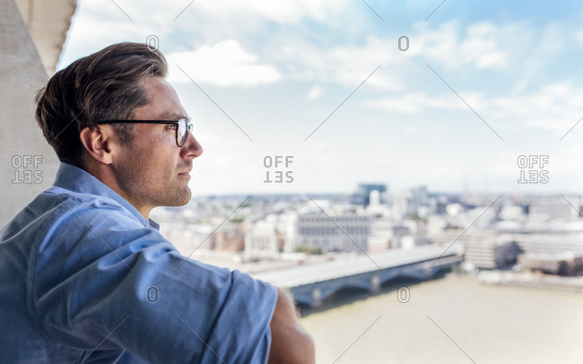 UK- London- man looking at the city on a roof terrace