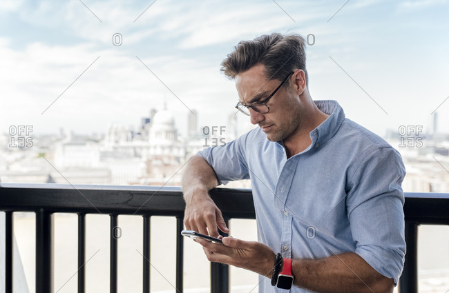 UK- London- man using cell phone on a roof terrace