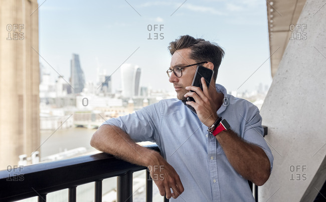 UK- London- man on the phone on a roof terrace