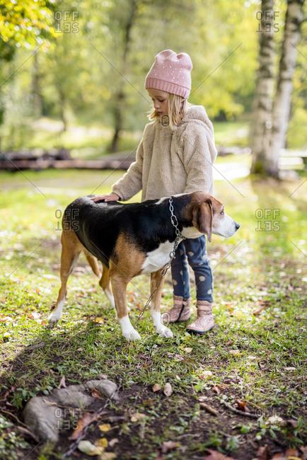Little girl stroking dog in autumnal garden