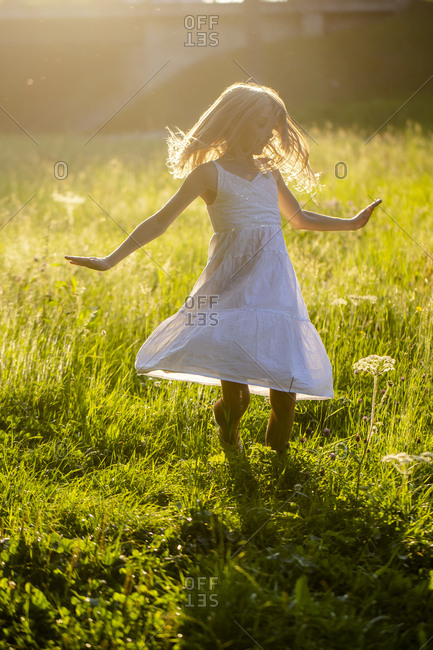 Happy girl dancing on summer meadow at backlight