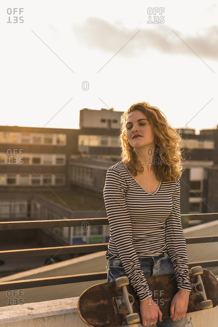 Portrait of young woman with skateboard enjoying sunset on roof terrace