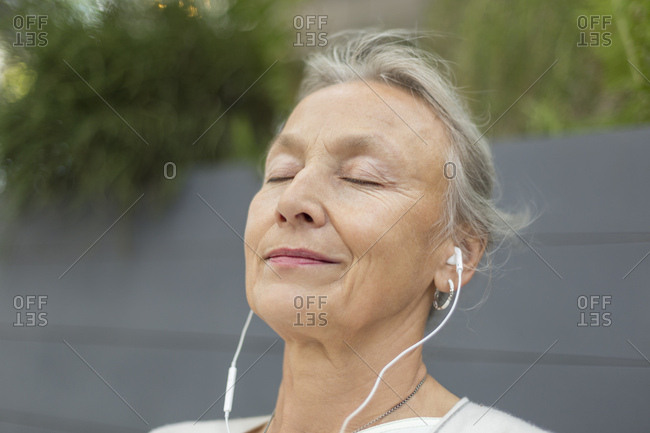 Portrait of senior woman with closed eyes wearing earphones outdoors